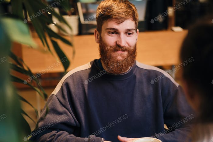 Young cheerful bearded man happily looking away on meeting in cozy cafe