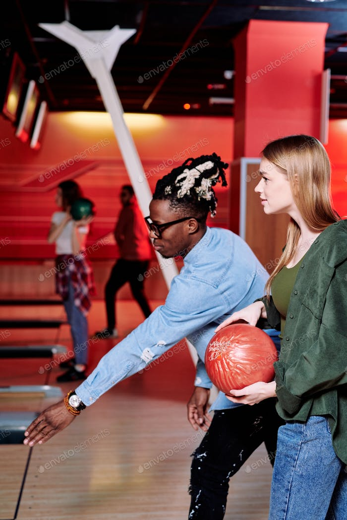 African guy with stretched arm explaining girlfriend how to throw bowling ball