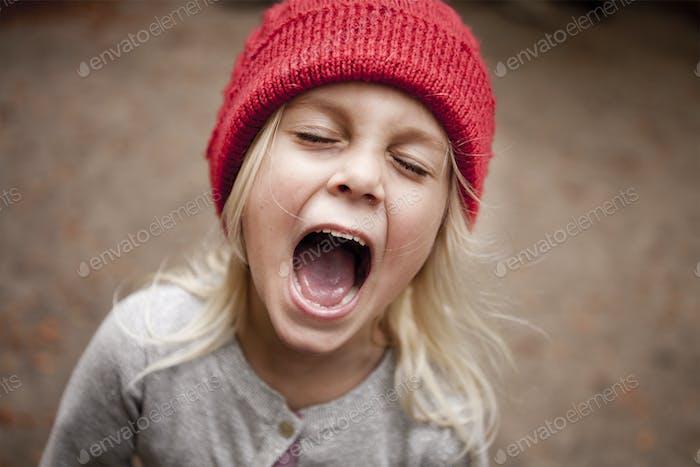 Chica juguetona gritando en el bosque