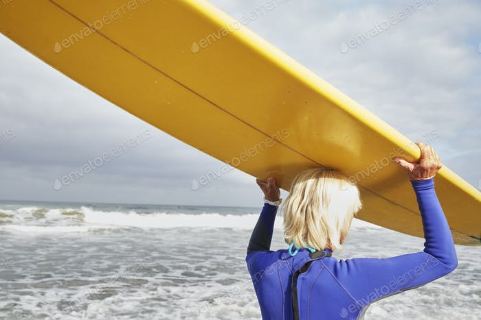 Senior woman on a beach, wearing a wetsuit and carrying a surfboard on her head.