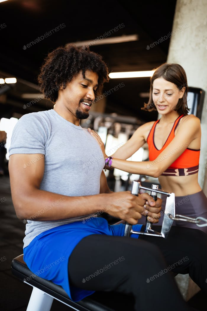 Fitness instructor exercising with client at the gym