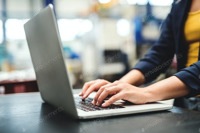 An industrial woman engineer in a factory with laptop, typing.
