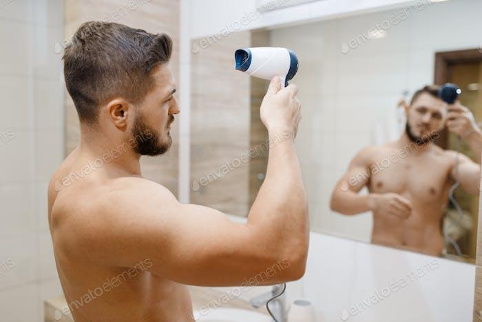 El hombre se seca el peinado con un secador de pelo