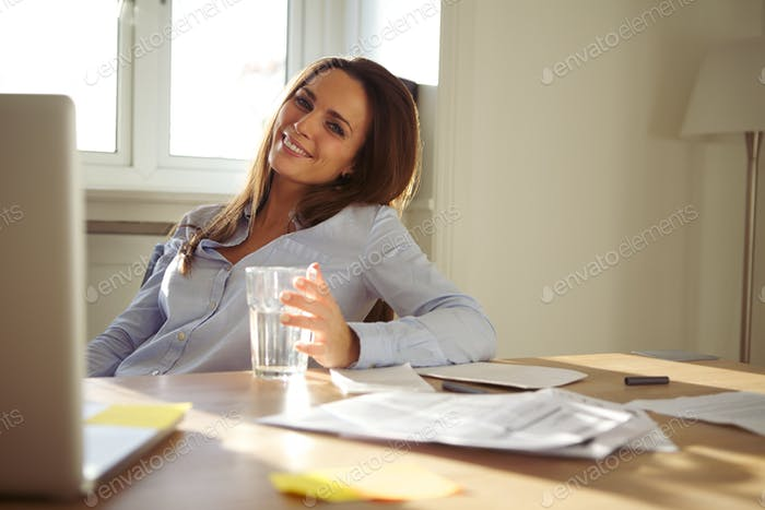 Woman working in home office smiling at camera