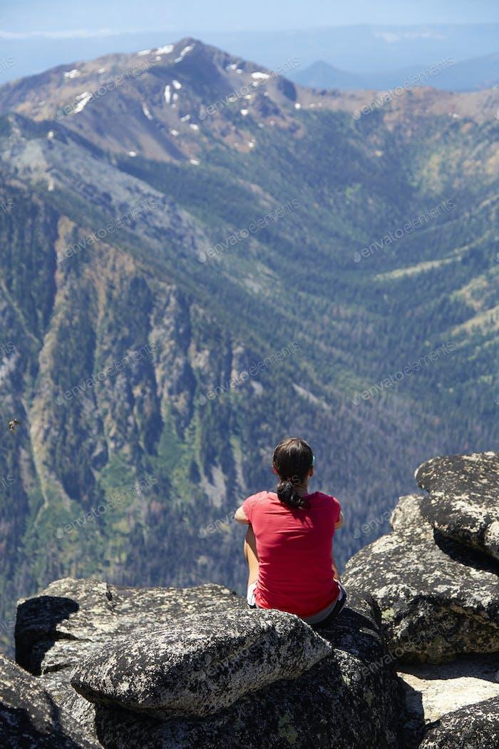 Hiker sitting on rocky hilltop