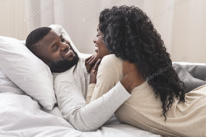 Smiling black couple having fun in bed, embracing and flirting