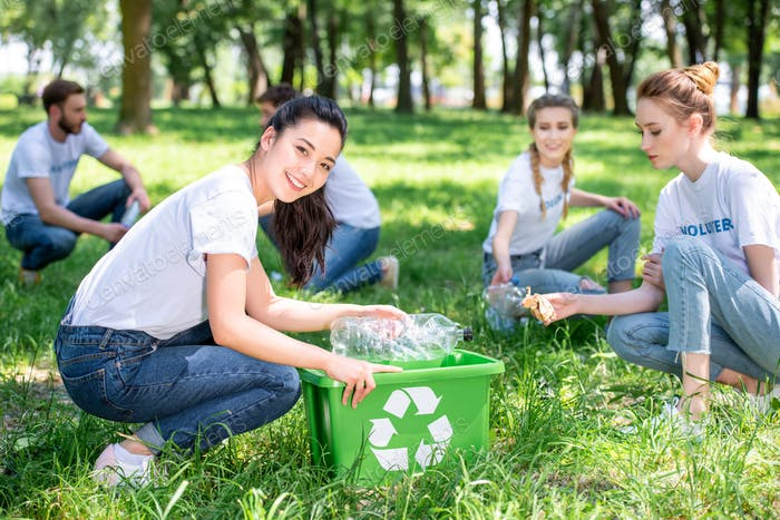 young smiling volunteers cleaning park with recycling box