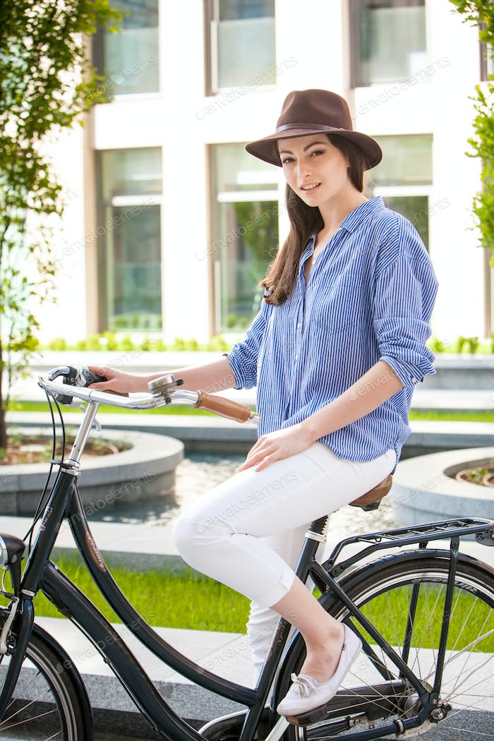 Pretty girl in hat riding a bicycle at street