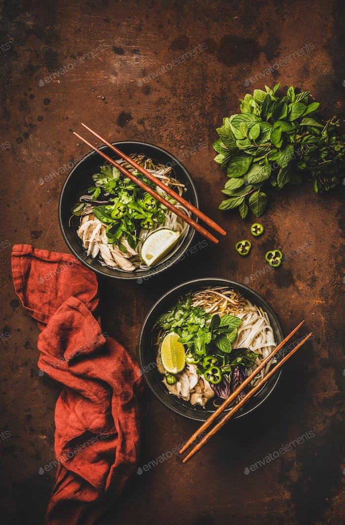 Vietnamesische asiatische traditionelle Reisnudel und Hühnersuppe in Schüsseln