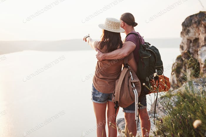 Two tourist male and woman with backpacks stand to the top of the mountain and enjoying sunrise