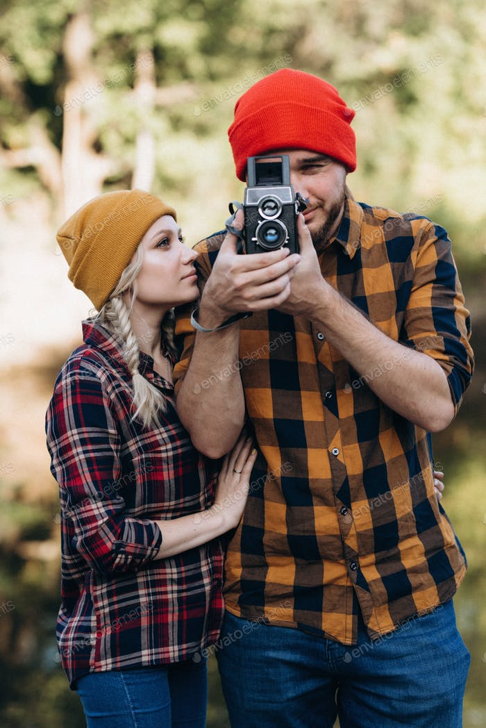 Bald guy with a beard and a blonde girl in bright hats are taking pictures with an old camera