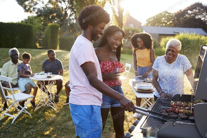 Couple grilling at a black multi generation family barbecue