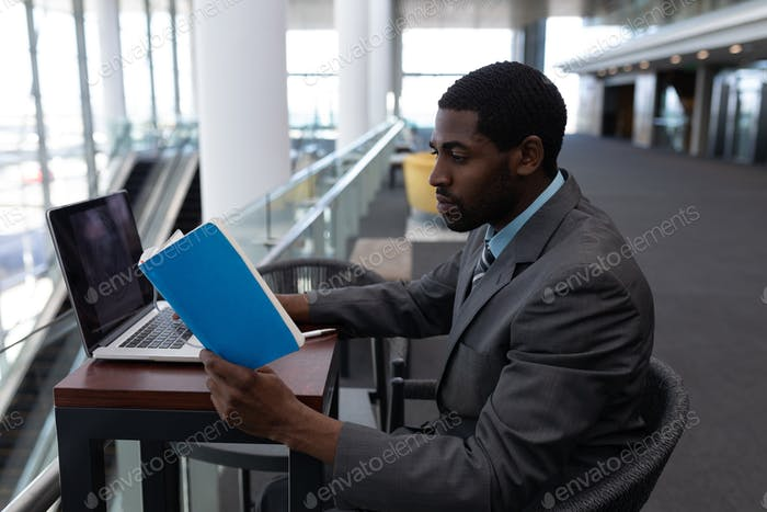 Businessman with laptop sitting at table and reading a book in modern office