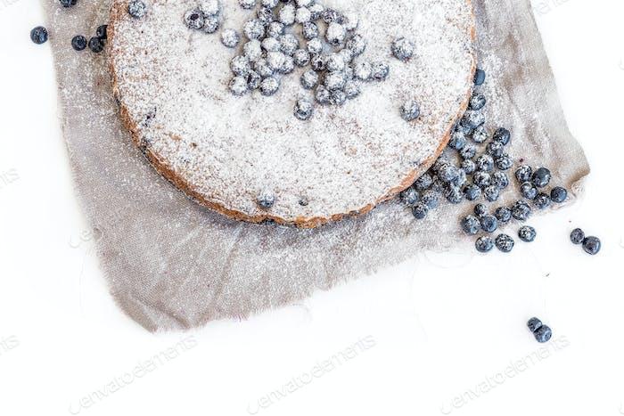 Blaubeerkuchen mit frischen Blaubeeren und Zuckerpulver auf einem Beige