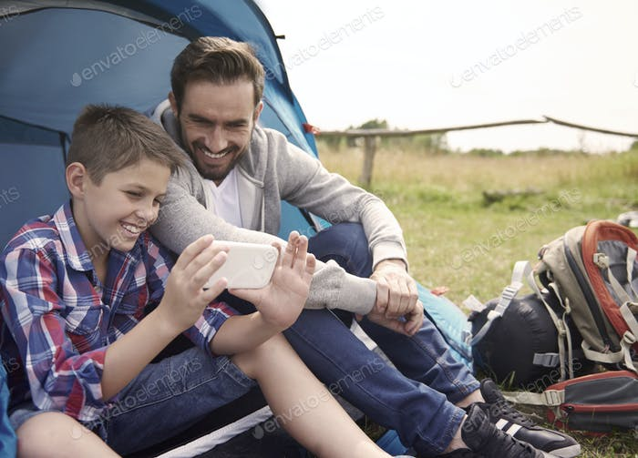 Boy using his smartphone on the camping