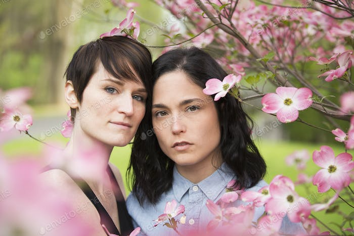 A same sex couple, two women under the branches of a flowering tree.