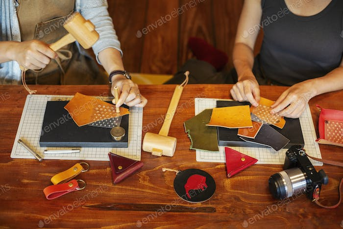 High angle view of two women sitting at a table, working in a leather shop.