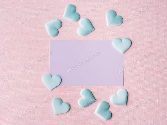 Lila Pastellkarte und Herzen auf rosa strukturierten Hintergrund