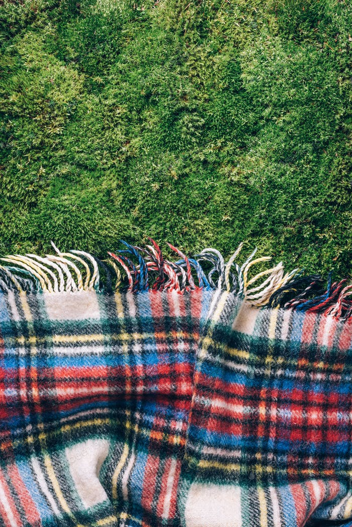 Checkered picnic plaid on green grass background. Top view. Copy space. Summer picnic time