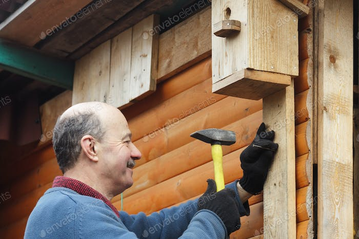 Bald senior with a mustache attaches bird house to the barn