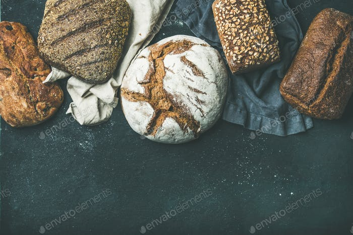 Various bread selection flat-lay, black background, copy space