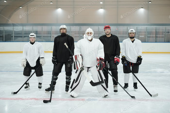 Professional hockey players and their trainer in sports uniform waiting for play