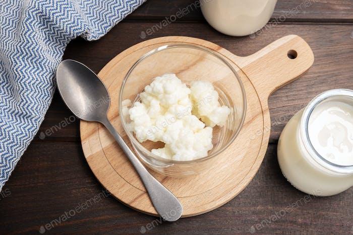 Milk kefir grains in jar on wooden table