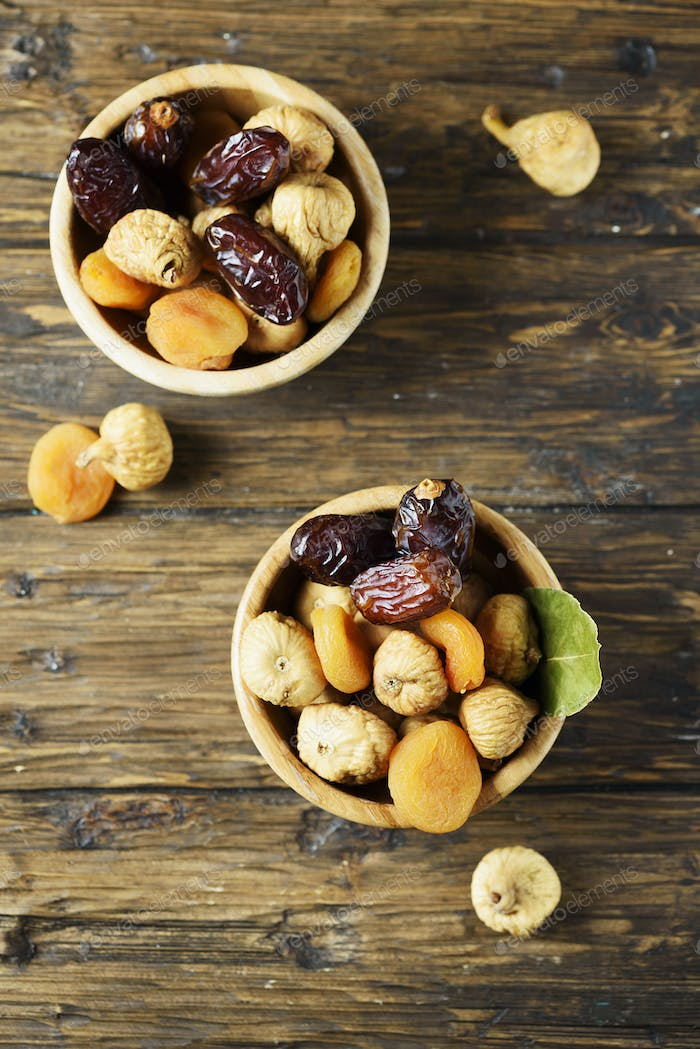 Sweet italian dried figs, apricots and dates on the wooden table