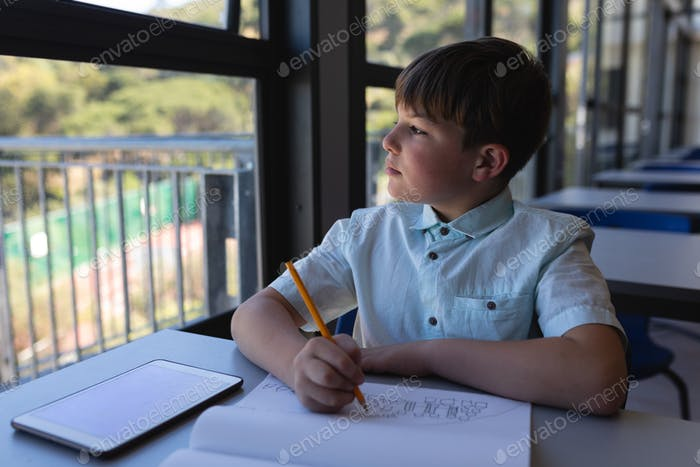 Schoolboy looking away while drawing on notebook at desk in classroom of elementary school