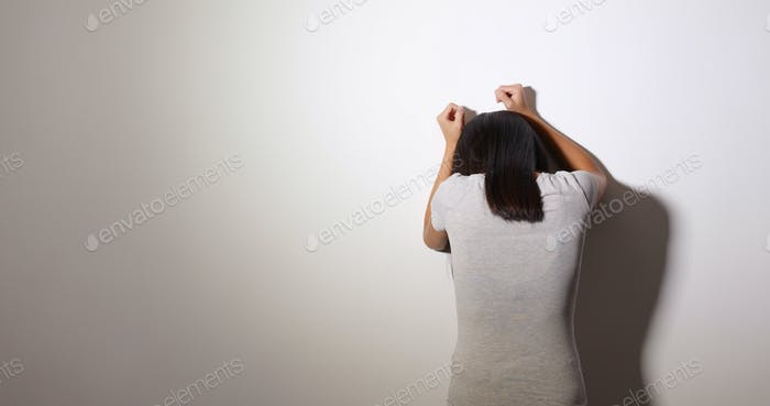 Woman feeling upset and cry against the wall