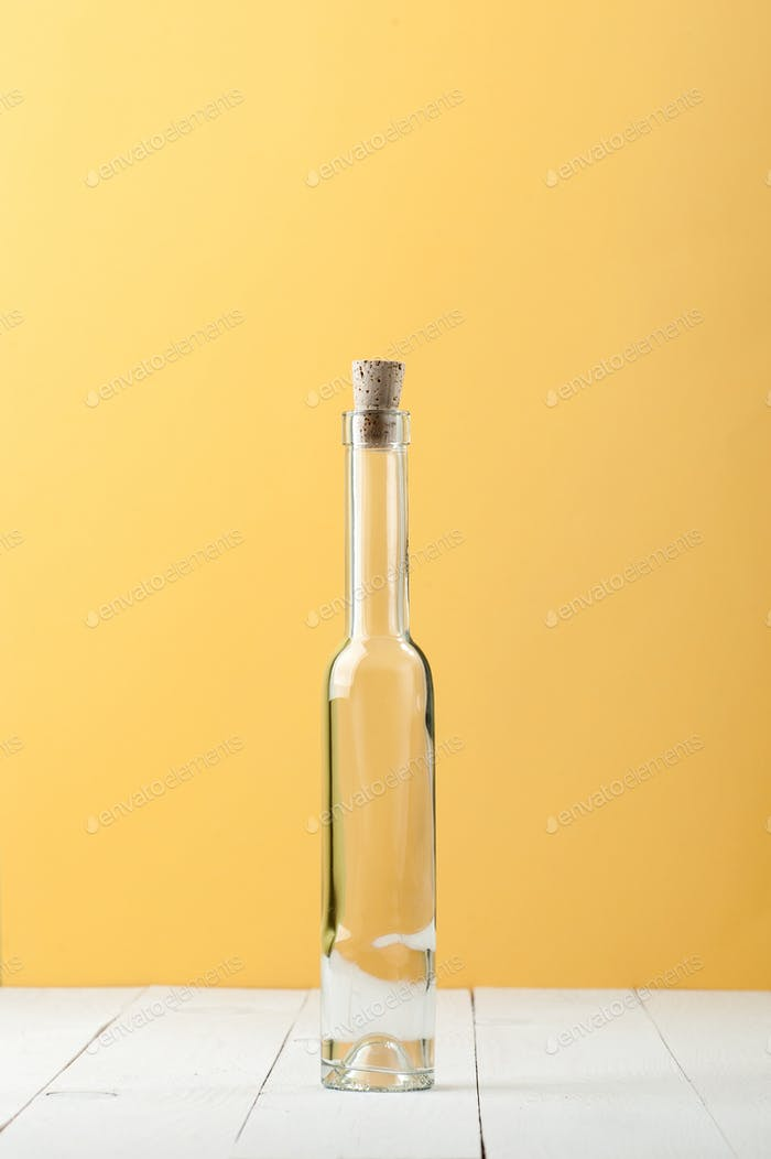 A narrow long glass bottle on a light white and yellow backgroun