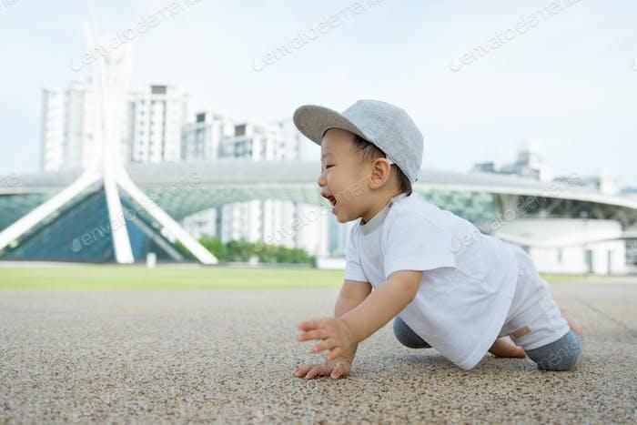 asiatische baby junge kriechen in park