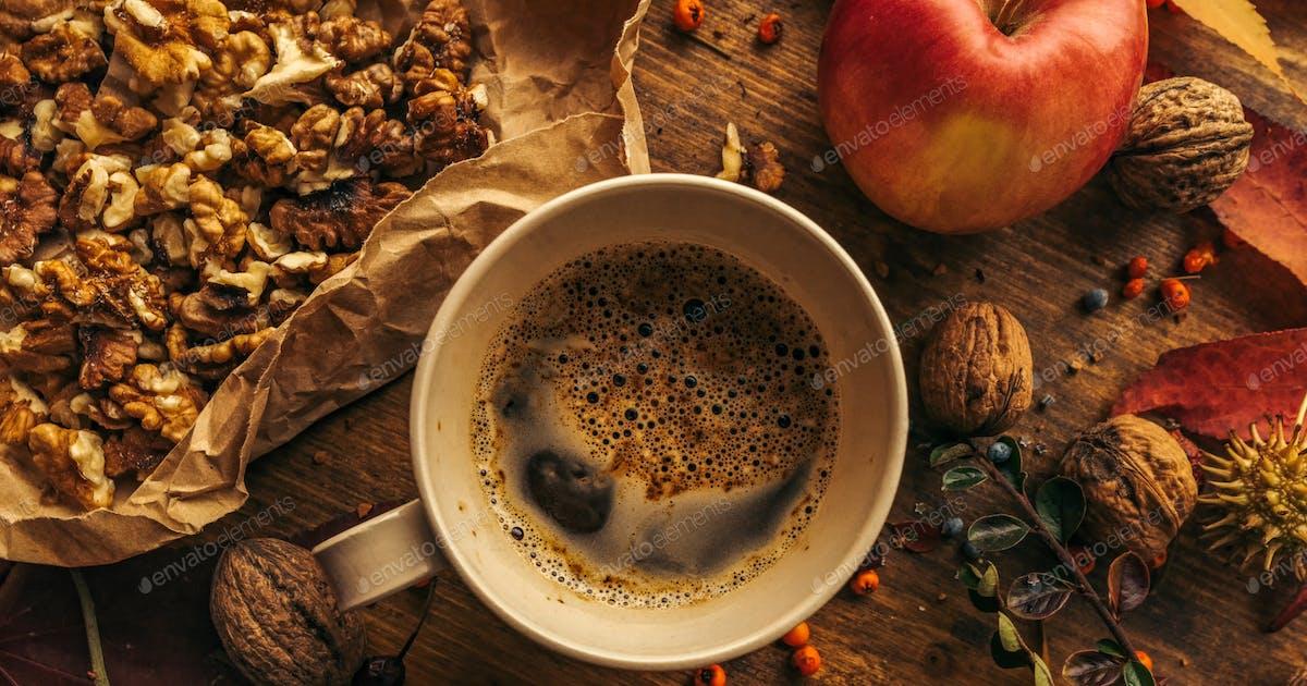 Enjoying fruits of autumn - apple, coffee and walnut on table photo