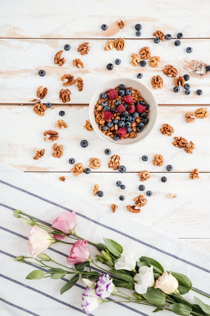 Flowers, napkin, cereals with berries and nuts on wooden background