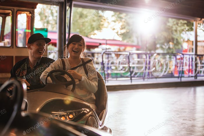 Young man and woman driving bumper car at fairground