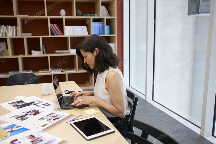 Woman in creative media office using laptop, horizontal