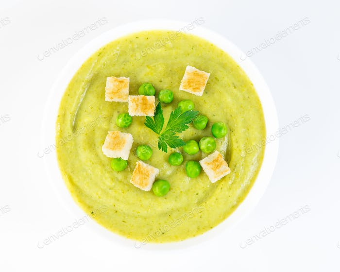 large white bowl with cream soup of broccoli, potatoes and green peas on white background, top view