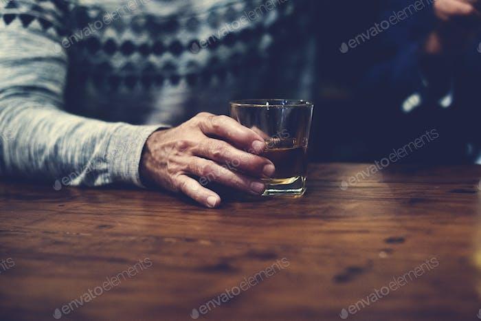 Ein Mann hält ein Glas Whisky