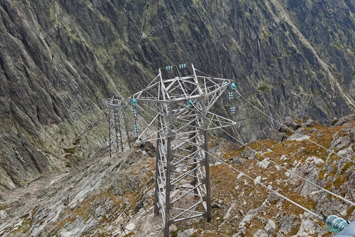 Electric power line in extremely high rocky mountains