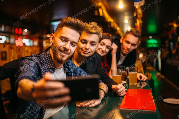 Happy football fans makes selfie at bar counter