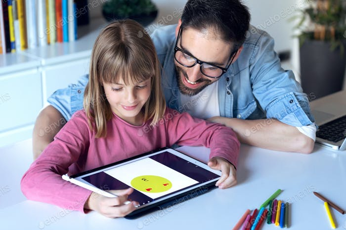 Schöner junger Vater mit seiner Tochter Zeichnung mit digitalem Tablet zu Hause.