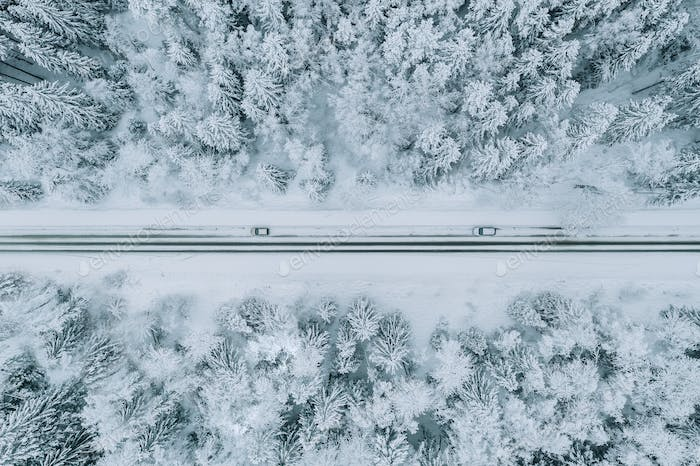 Aerial view of road with car in winter forest with snow.