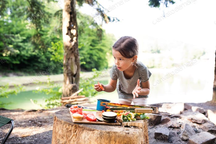 Little girl camping in forest eating grilled food.