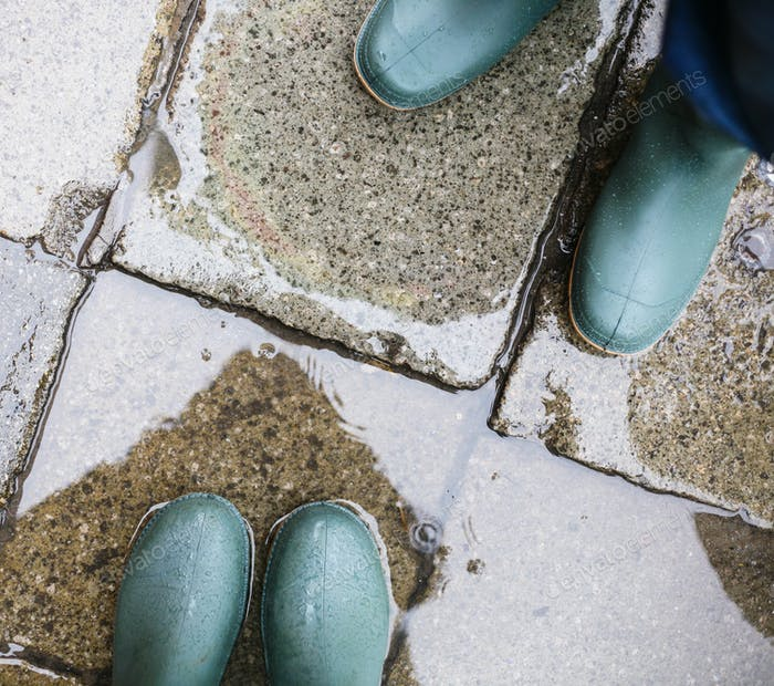 legs in green rubber boots in puddle