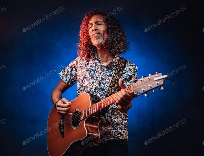 Talented hispanic musician in a hawaiian shirt playing guitar on a dark