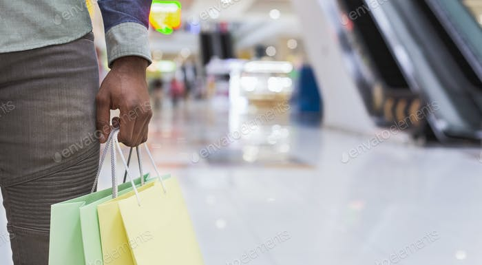 Unrecognizable african man holding shopping bags in city mall