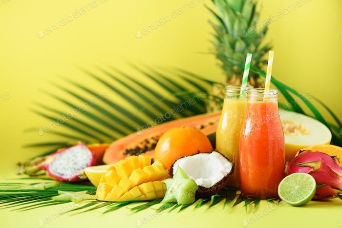 Saftige Papaya und Ananas, Mango, Orangenfrucht-Smoothie in zwei Gläsern auf gelbem Hintergrund. Entgiftung