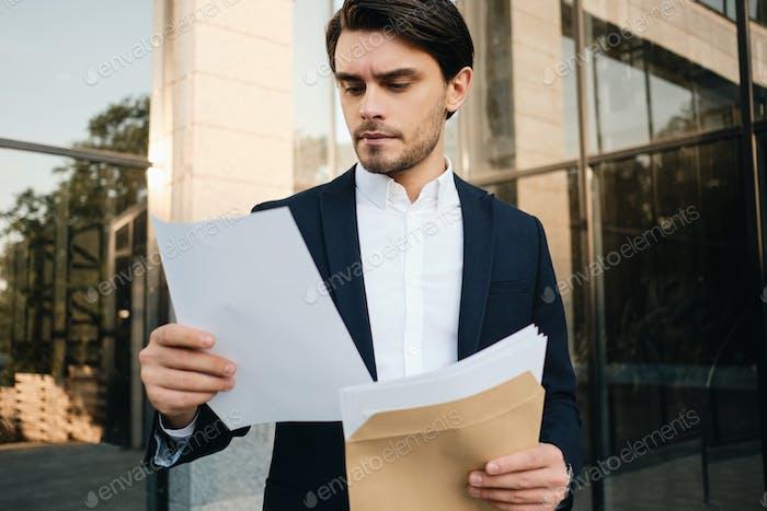 Junger Mann in klassischer Jacke nachdenklich lesen Dokumente aus Postumschlag in der Nähe von Bürozentrum