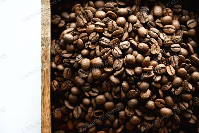Raw and roasted coffee beans in wooden box. Ingredients for coffee beverage. Food background