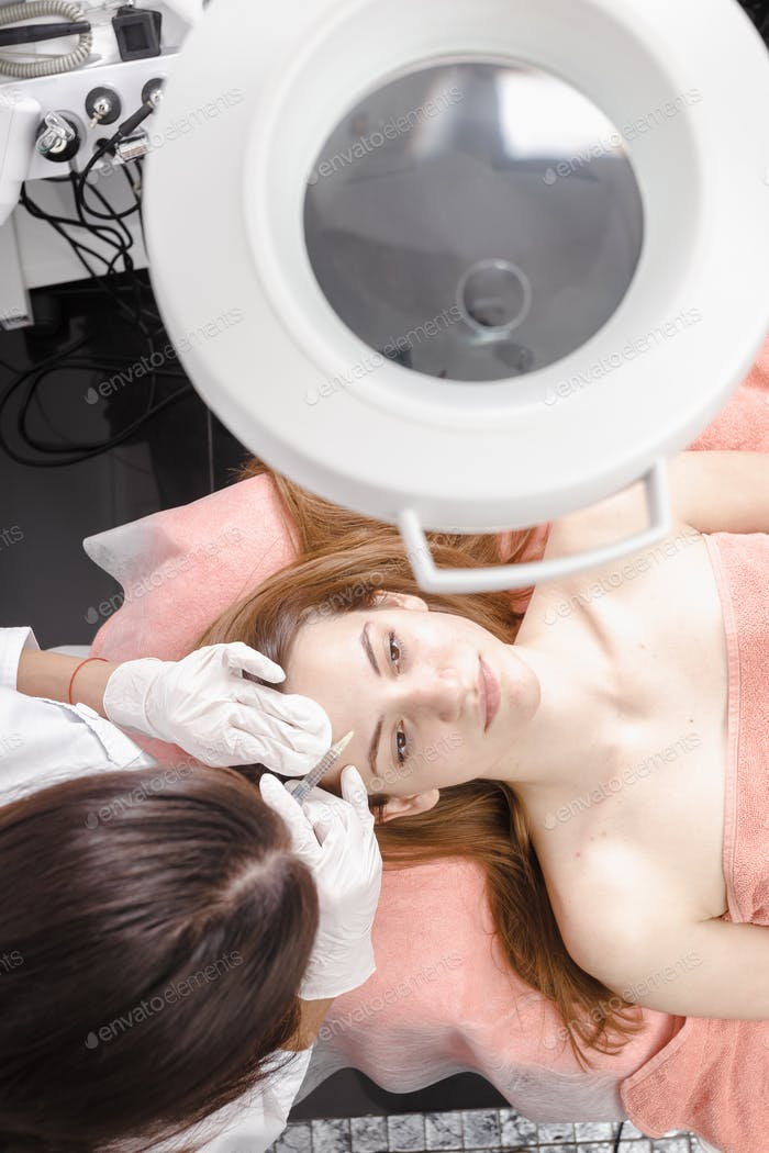 Young woman getting dermall fillers injection